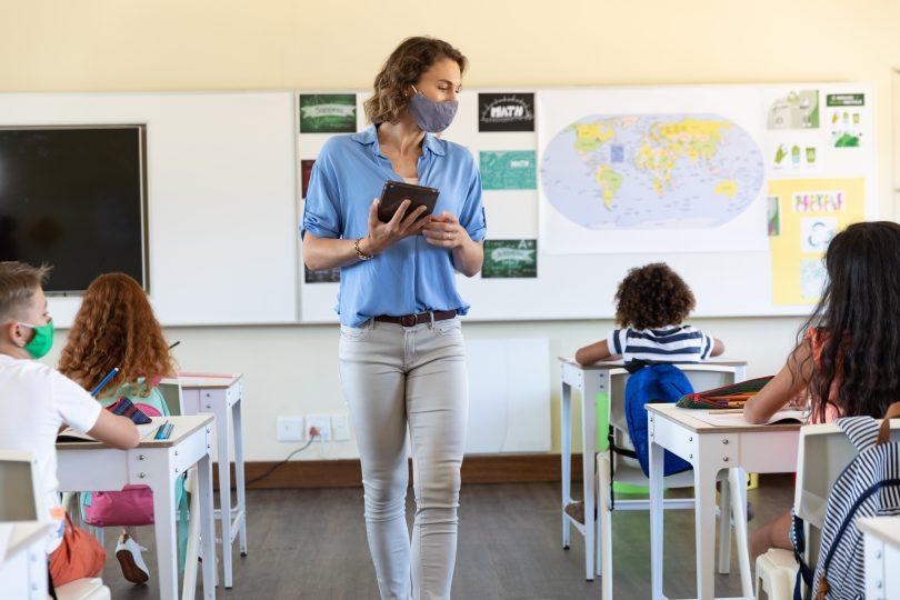 Lehrerin unterrichtet ihre Klasse während der Corona-Krise mit Maske
